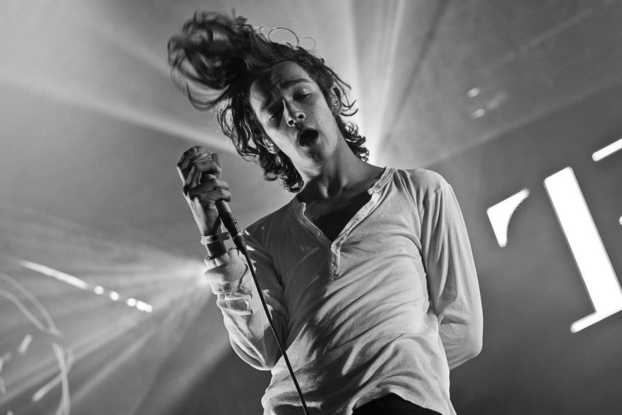 The 1975's Matty Healy returns to stage in a hospital gown after serious illness