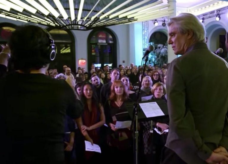 David Byrne performs an emotional cover of David Bowie's 'Heroes' with a huge choir