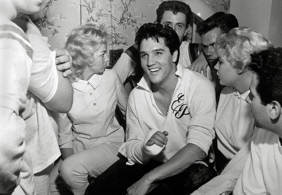 Elvis Presley at a hospital surrounded by his fans after injuring his finger,circa 1957